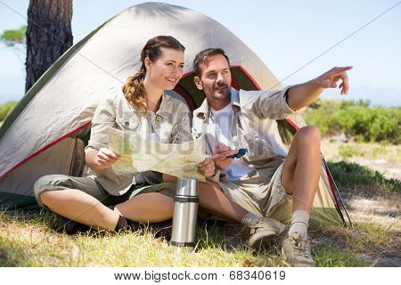Outdoorsy couple looking at the map and pointing outside tent on a sunny day