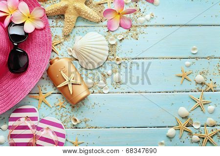 summer background with sunglasses, hat and flip flops on wooden board