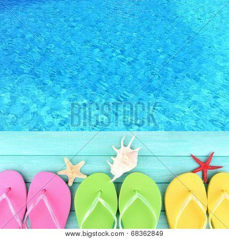Colored flip flops on wooden platform beside sea