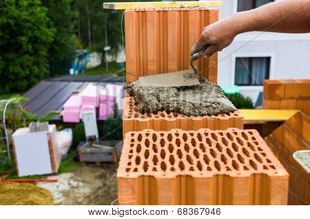 anonymous construction worker on a construction site building a house built a wall of bricks. brick wall of a solid house. icon image for undeclared work and bungling
