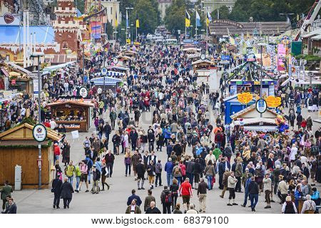 MUNICH, GERMANY - SEPTEMBER 30, 2013: Visitors explore the Theresienwiese Oktoberfest fair grounds. The 16 day festival has been annually celebrating beer since 1810.