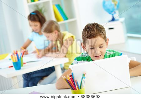 Portrait of smart lad at workplace networking with two classmates drawing on background