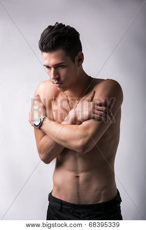 Shirtless Young Man Hugging Himself