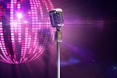 Retro microphone on stand against digitally generated cool disco ball design poster