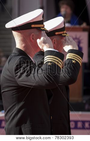 NEW YORK - NOV 11, 2014: Two commanders from the US Navy salute as they march past the VIP stage during the 2014 America's Parade held on Veterans Day in New York City on November 11, 2014.