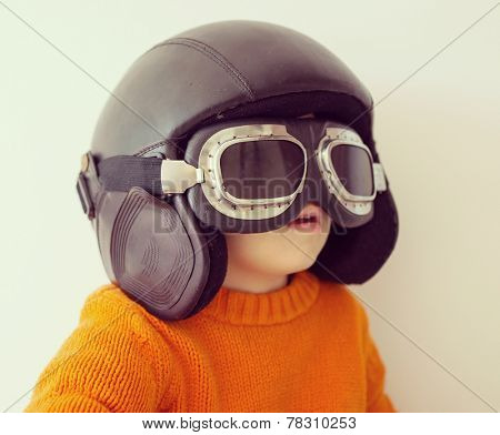 Little cute playful baby kid with pilot hat and goggles ready for airplane flying poster