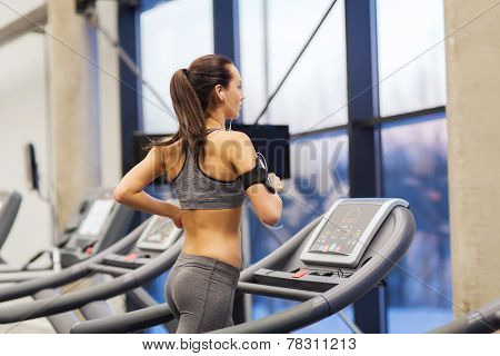 sport, fitness, lifestyle, technology and people concept - woman with smartphone or player and earphones exercising on treadmill in gym poster
