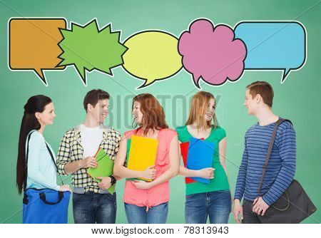 school, education, communication and people concept - group of smiling teenagers with folders and school bags talking over green board background with text bubbles