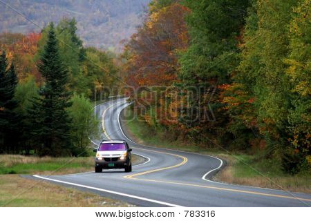A car driving along a winding road in Vermont poster