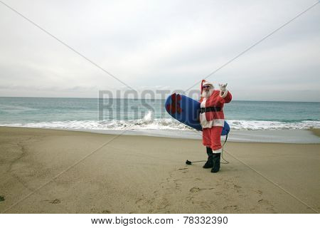 Surfing Santa Claus. Santa Claus holds his Blue Surfboard under his arm as he checks out the Waves at one of his Favorite Secret Surfing Spots. Santa loves Sports and Surfing. They call him Mr. Claus