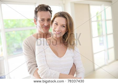 Cheerful 40-year-old couple embracing each other at home