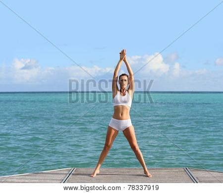 Woman doing stretching exercises in pontoon by the sea poster