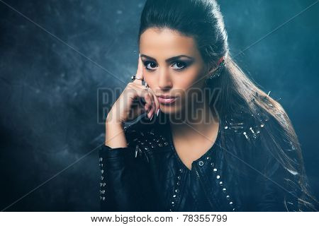 young beautiful woman portrait in black leather jacket with studs, studio shot poster