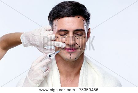 Handsome man with closed at plastic surgery with syringe in his face