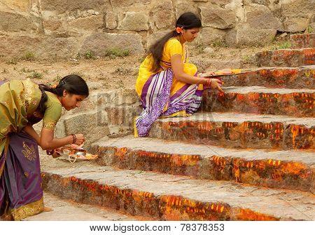 Hindu devotees apply kumkuma to the temple steps during annual event Bonalu festival