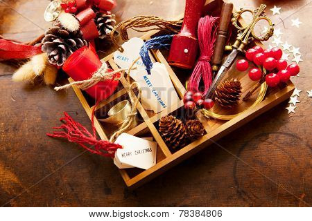 Christmas preparation. Tray with ribbons and christmas tags, on an old wooden table.