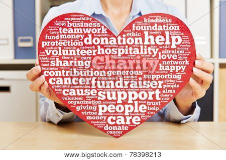 Hands holding heart with charity and fundraiser tag cloud