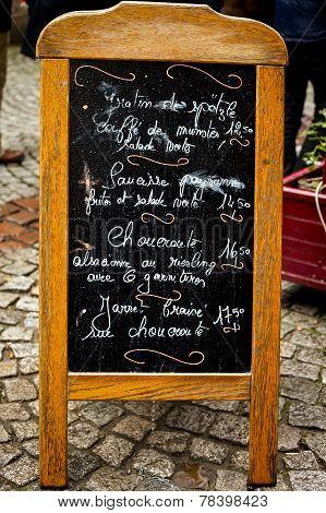 French menu board on cobblestones