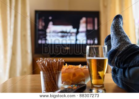 Television TV watching (movie) with feet on table and huge amounts of snacks - stock photo poster