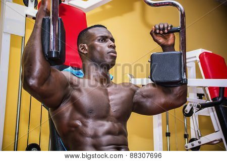 Hunky muscular black bodybuilder working out in gym, exercising pecs on machine poster