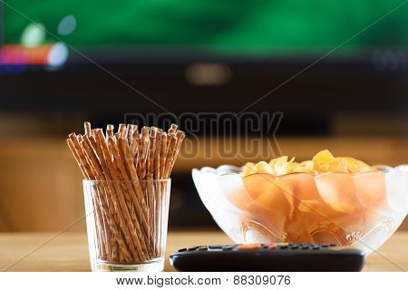 television TV watching (football soccer match) with snacks lying on table - stock photo poster