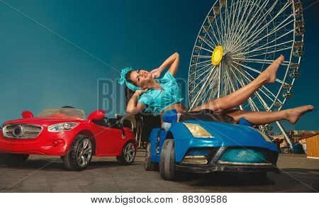 Pretty woman driving toy car.  Amusement park at night - ferris wheel  in motion
