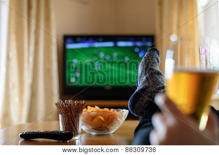 Television TV watching (football match) with feet on table and huge amounts of snacks - stock photo poster