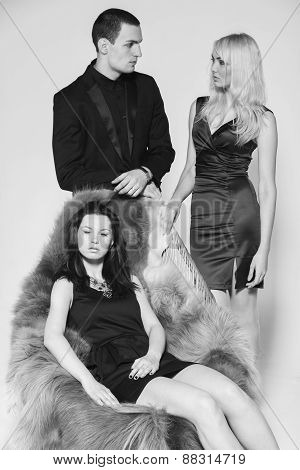 The relationship between man and woman. The concept of a love triangle. Human emotions - jealousy, betrayal, jealousy, love. Two beautiful girls and a guy on a black leather couch. poster
