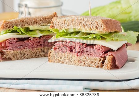 sandwich with roast beef, cheese, mustard and lettuce on whole wheat italian bread