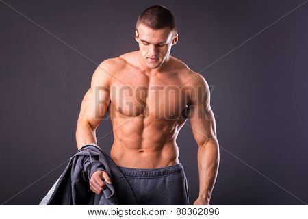 Bodybuilder showing his press. A man shows his abdominal muscles, raised his hand t-shirt. Presss, muscles, show, bodybuilding. Sports guy. poster