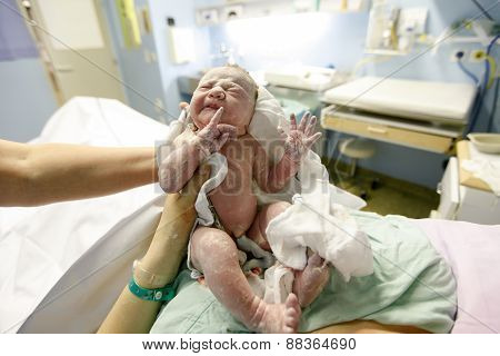 Mother and midwife holding a newborn baby covered in vernix right after the delivery. Maternity hospital delivery room baby being photographed for the first time with umbilical cord still attached. poster
