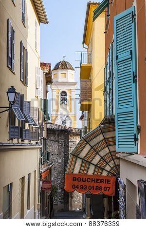 VILLEFRANCHE-SUR-MER, FRANCE - OCTOBER 4, 2014: Narrow street leading to Eglise Saint-Michel (Saint Michael's Church) is framed by colourful buildings and quaint shops.