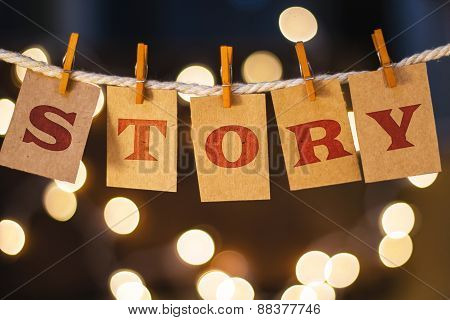 The word STORY printed on clothespin clipped cards in front of defocused glowing lights. poster