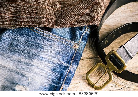 Detail Of An Unbuckled Leather Belt On A Faded Pair Of Blue Jeans