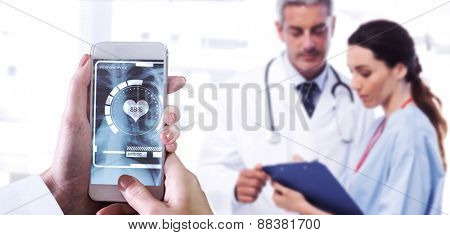 Hand holding smartphone against nurse and doctor looking a file