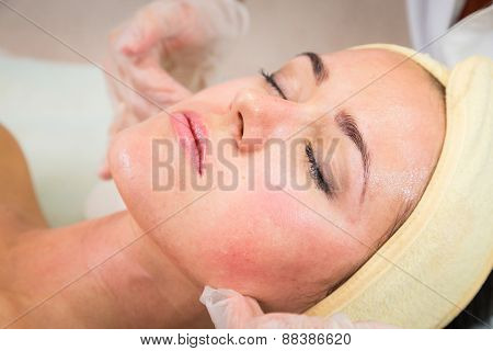 Beautiful woman with facial mask at beauty salon.Pretty woman receiving facial massage.Spa therapy for young woman receiving facial mask at beauty salon - indoors poster