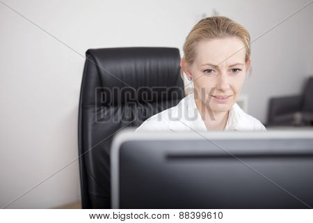 Adult Female Doctor Looking At Her Computer Screen