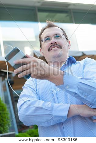 Urban man using smart phone outside using app on 4g wireless device wearing headphones. Adult urban