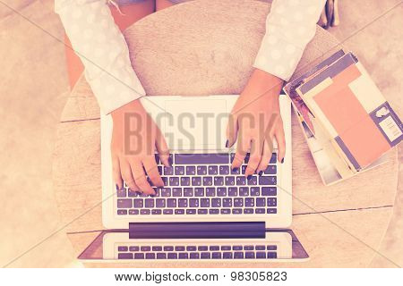 Girl At The Table Typing On A Laptop, Vintage Photo Effect