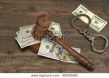 Dollar Cash, Handcuffs And Judge Gavel On Wood Table