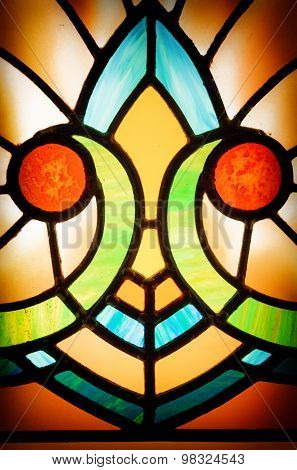 Detail of an old, 1920s style Art Deco window. Colourful stained glass texture with vignette.