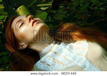 Tender young woman swinning in the pond among water lilies basking in the sun in shallow waters poster