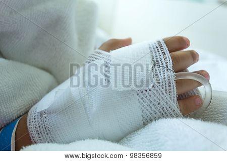 Hand illness asian kids a sickbed, saline intravenous (IV) on hand