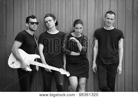 Music band outdoor portrait. Musicians and woman soloist posing outside against grunge fence, black and white.