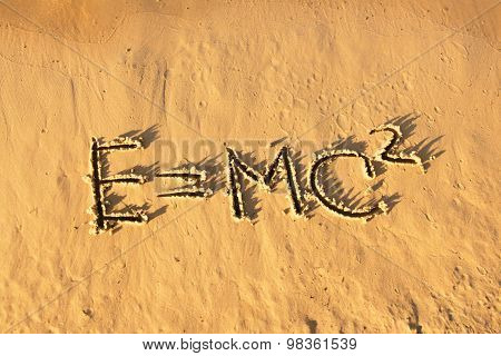 Einstein's formula handwriting on the sand. Sunset on the beach. poster