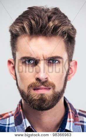 Closeup portrait of a serious man looking at camera isolated on a white background