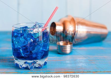 Cool refreshing blue curacao cocktail in pounchy glass with cubes of ice and shaker on a wooden back