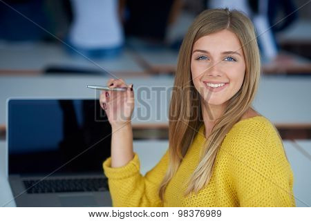 portrait of happy smilling student girl at tech classroom with laptop computer in background