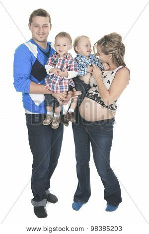 Young family with pregnant mom posing in studio on white backgro