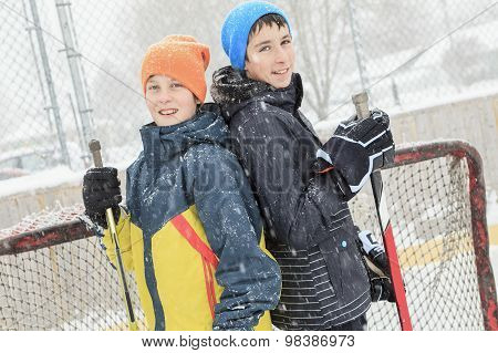 a brother playing hockey outside on a ice rink. poster